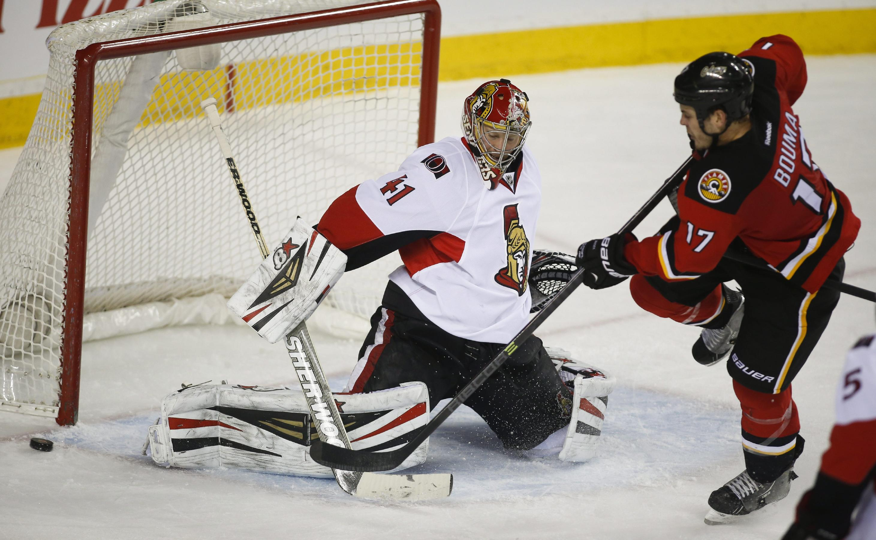 Ottawa Senators goalie Craig Anderson, left, kicks away a shot from Calgary Flames' Lance Bouma during third period NHL hockey action in Calgary, Alberta, Wednesday, March 5, 2014. The Calgary Flames beat the Ottawa Senators 4-1