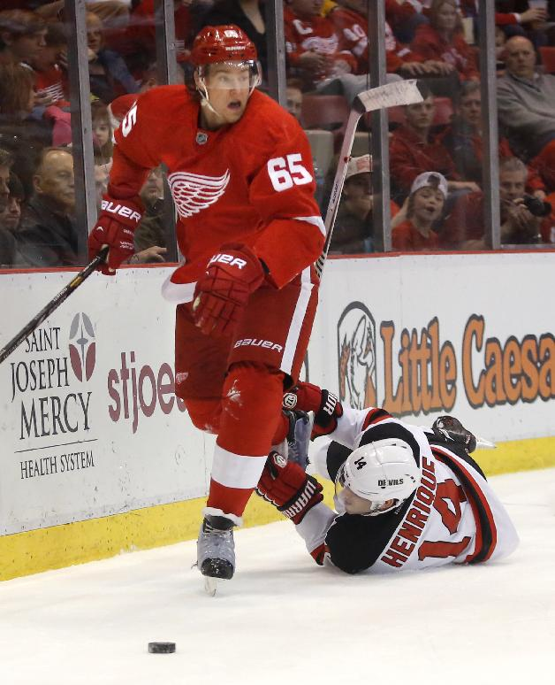 New Jersey Devils' Adam Henrique (14) tries to trip up Detroit Red Wings' Danny DeKeyser (65) during the first period of an NHL hockey game Friday, March 7, 2014, in Detroit