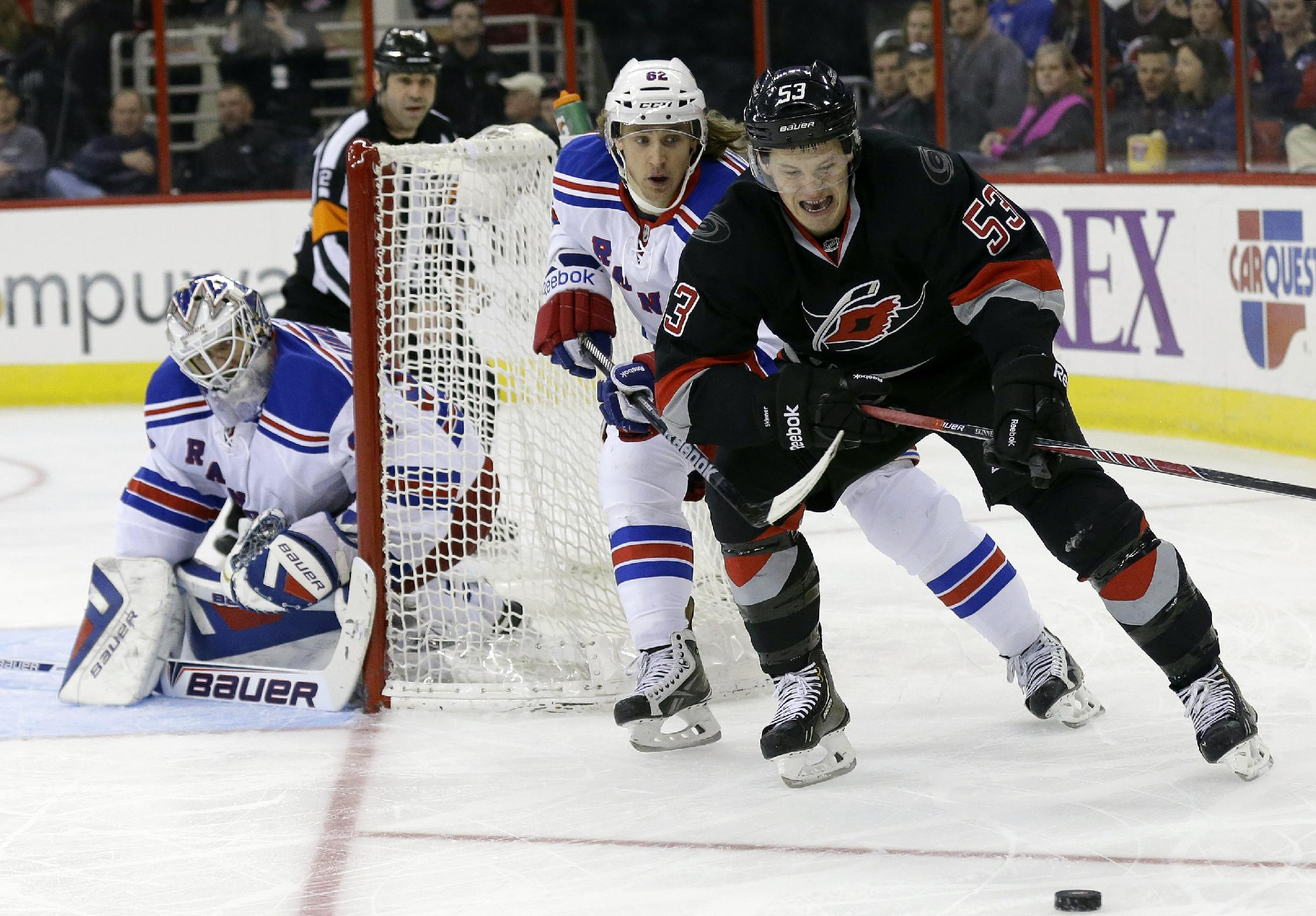 Carolina Hurricanes' Jeff Skinner (53) chases the puck as New York Rangers' Carl Hagelin (62) and goalie Henrik Lundqvist, of Sweden, defend the goal during the second period of an NHL hockey game in Raleigh, N.C., Friday, March 7, 2014