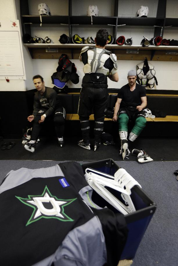 Dallas Stars' Ray Whitney, left, Shawn Horcoff, center, and Jamie Benn take off equipment following an NHL hockey practice Tuesday, March 11, 2014, in St. Louis. Dallas Stars' Rich Peverley is undergoing testing to determine what triggered his collapse during a game Monday night in Dallas. The Stars are scheduled to play the St. Louis Blues tonight in St. Louis
