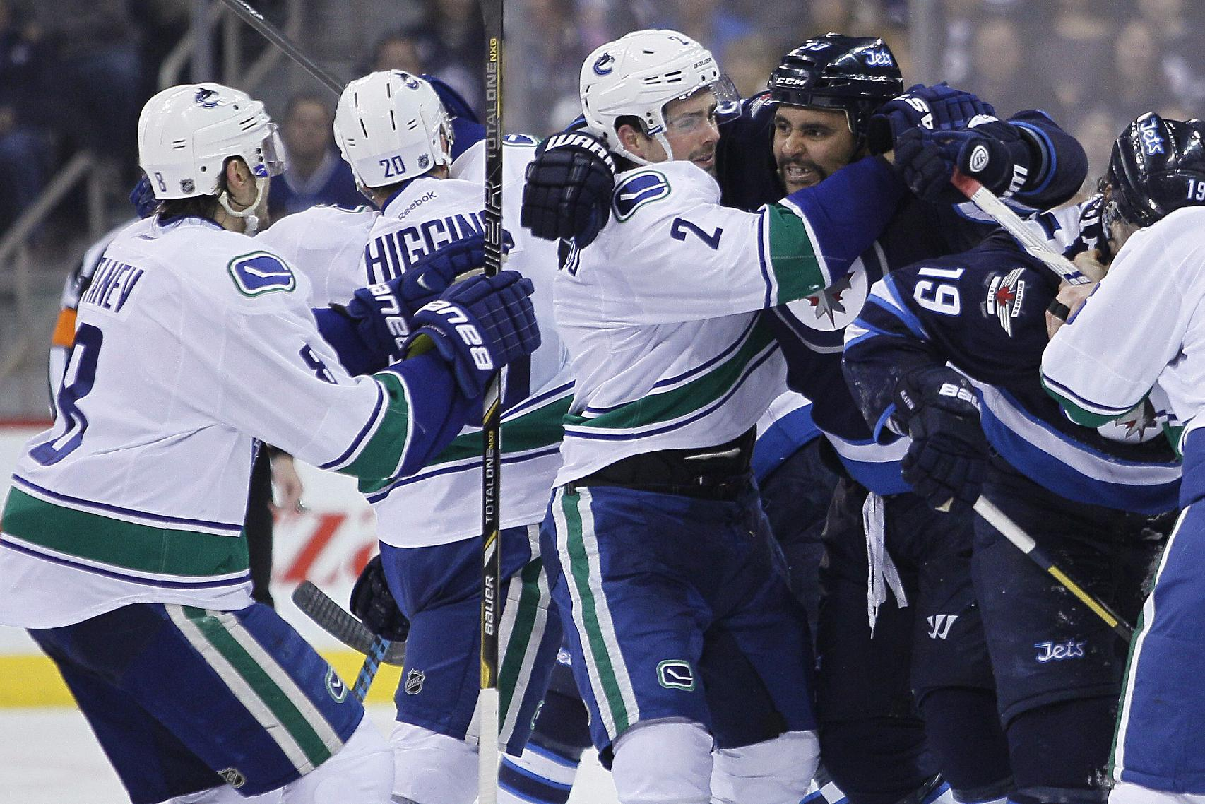 Vancouver Canucks' Shawn Matthias (27) holds back Winnipeg Jets' Dustin Byfuglien (33) from Canucks' Christopher Tanev (8) during the second period of an NHL hockey game Wednesday, March 12, 2014, in Winnipeg, Manitoba