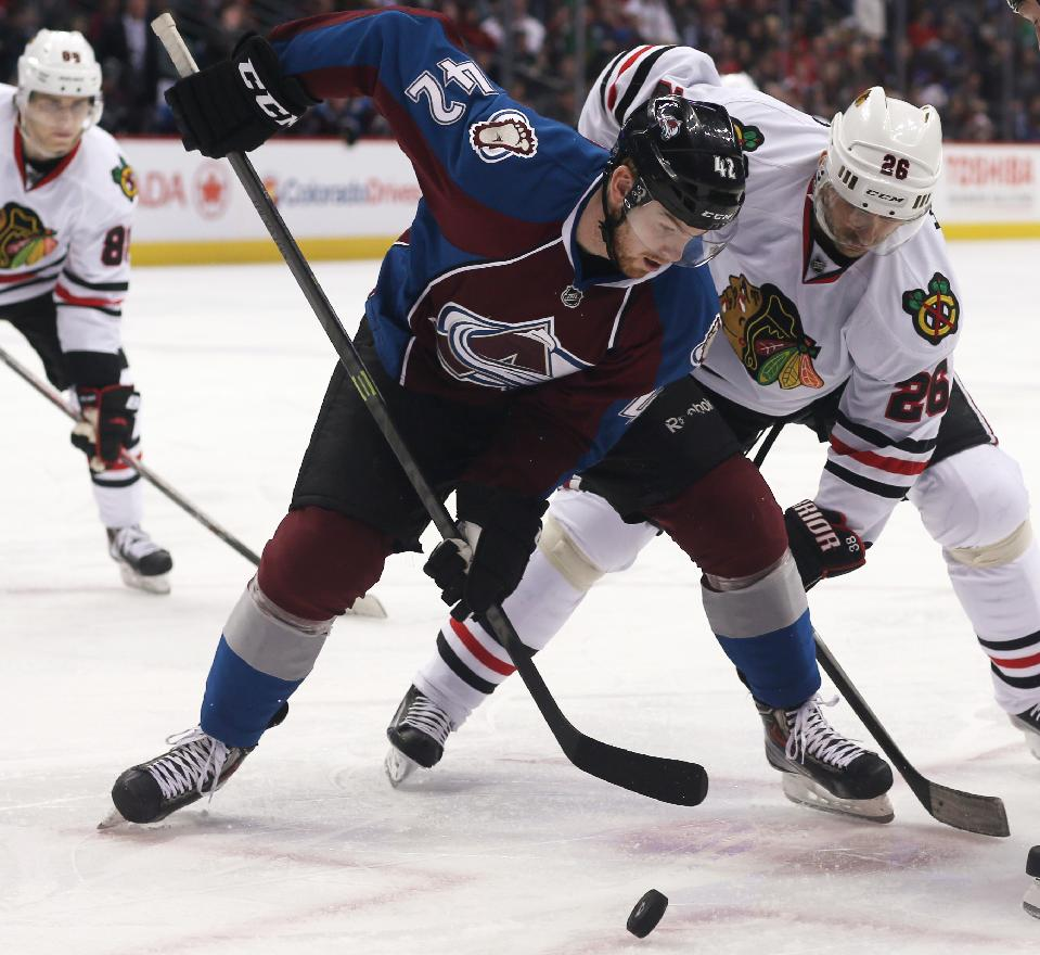 Colorado Avalanche center Brad Malone, front, battles for control of the puck with Chicago Blackhawks center Michal Handzus, of Slovakia, in the second period of an NHL hockey game in Denver on Wednesday, March 12, 2014