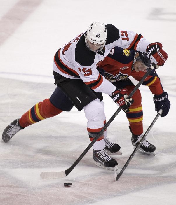New Jersey Devils' Travis Zajac (19) and Florida Panthers' Nick Bjugstad, right, battle for the puck  during the first period of an NHL hockey game, Friday, March 14, 2014, in Sunrise, Fla