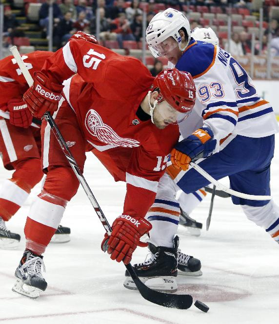 Detroit Red Wings' Riley Sheahan (15) wins the faceoff against Edmonton Oilers' Ryan Nugent-Hopkins (93) during the first period of an NHL hockey game Friday, March 14, 2014, in Detroit