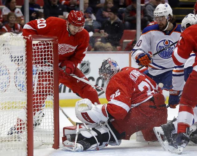 Detroit Red Wings goalie Jimmy Howard (35) stops a shot during a scrum at the net against Edmonton Oilers' Luke Gazdic, right, as Detroit Red Wings' Drew Miller, left, helps defend during the first period of an NHL hockey game Friday, March 14, 2014, in Detroit