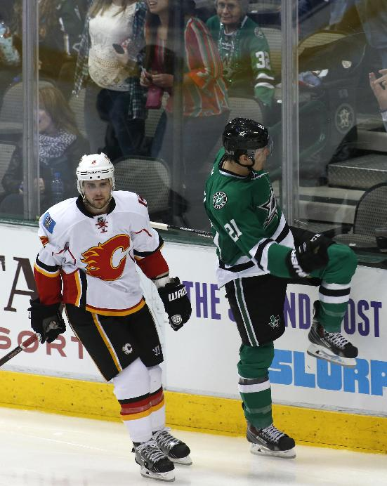 Calgary Flames defenseman Kris Russell (4) skates away as Dallas Stars left wing Antoine Roussel (21), of France, celebrates his goal in the second period of an NHL hockey game on Friday, March 14, 2014, in Dallas