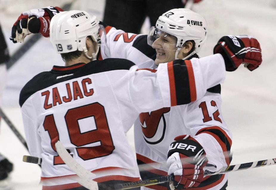 CORRECTS TO GOAL SCORED BY JAGR, NOT BRUNNER - New Jersey Devils' Damien Brunner (12), of Switzerland, celebrates with teammate Travis Zajac (19)after Jaromir Jagr scored a goal during the first period of an NHL hockey game against the Florida Panthers, Friday, March 14, 2014, in Sunrise, Fla