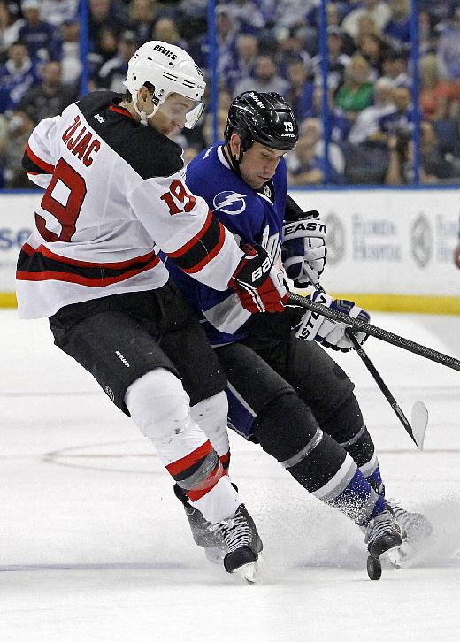 New Jersey Devils center Travis Zajac, left, and Tampa Bay Lightning right wing B.J. Crombeen race for the puck during the third period of an NHL hockey game Saturday, March 15, 2014, in Tampa, Fla. The Lightning won 3-0