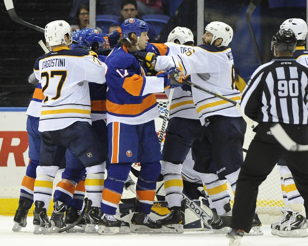 New York Islanders' Matt Martin (17) and Buffalo Sabres' Mike Weber (6) together with other players scuffle in front of the net in the third period of an NHL hockey game on Saturday, March 15, 2014, in Uniondale, N.Y. The Islanders won 4-1