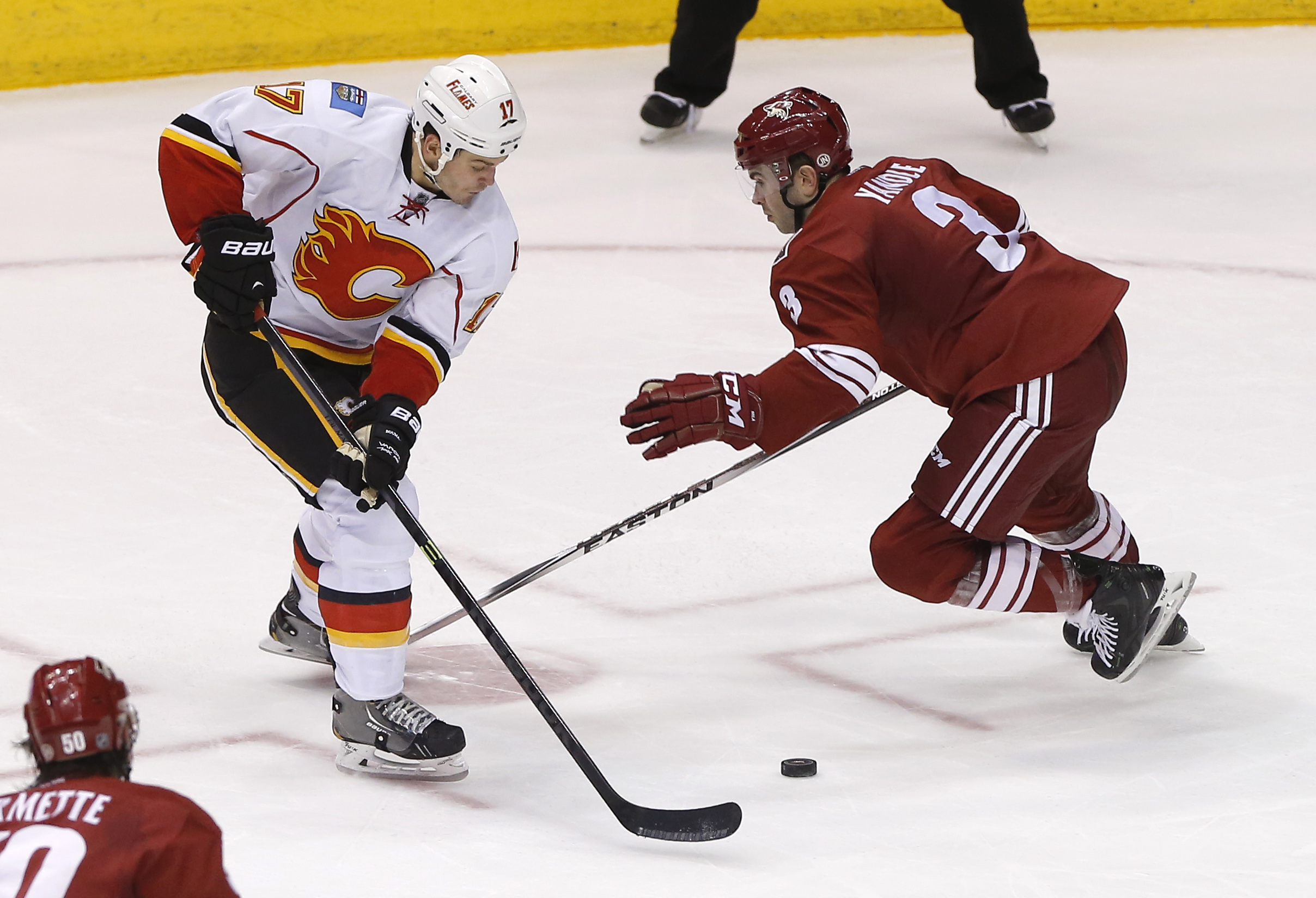 Calgary Flames' Lance Bouma (17) and Phoenix Coyotes' Keith Yandle (3) battle for the puck during the second period of an NHL hockey game, Saturday, March 15, 2014, in Glendale, Ariz