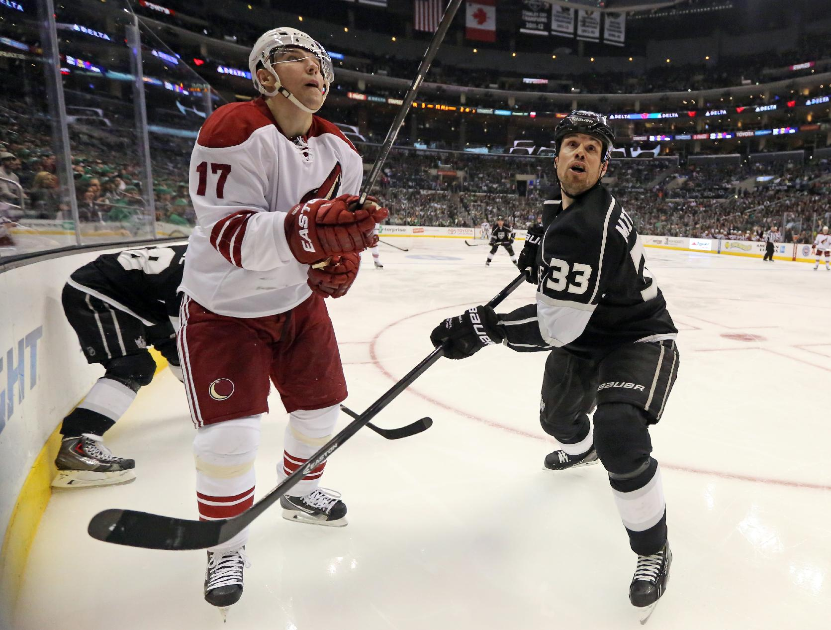Phoenix Coyotes right winger Radim Vrbata (17), of the Czech Republic, and Los Angeles Kings defenseman Willie Mitchell (33) watch the puck sail high in the third period of an NHL hockey game in Los Angeles Monday, March 17, 2014.  The Coyotes won, 4-3