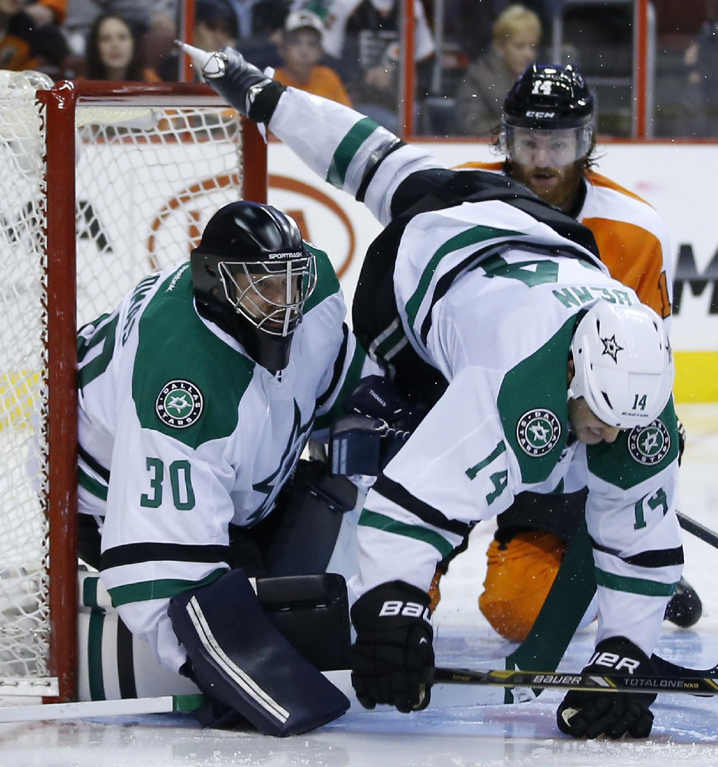 Dallas Stars' Jamie Benn (14) flies into goalie Tim Thomas (30) after colliding with Philadelphia Flyers' Sean Couturier (14) during the second period of an NHL hockey game, Thursday, March 20, 2014, in Philadelphia