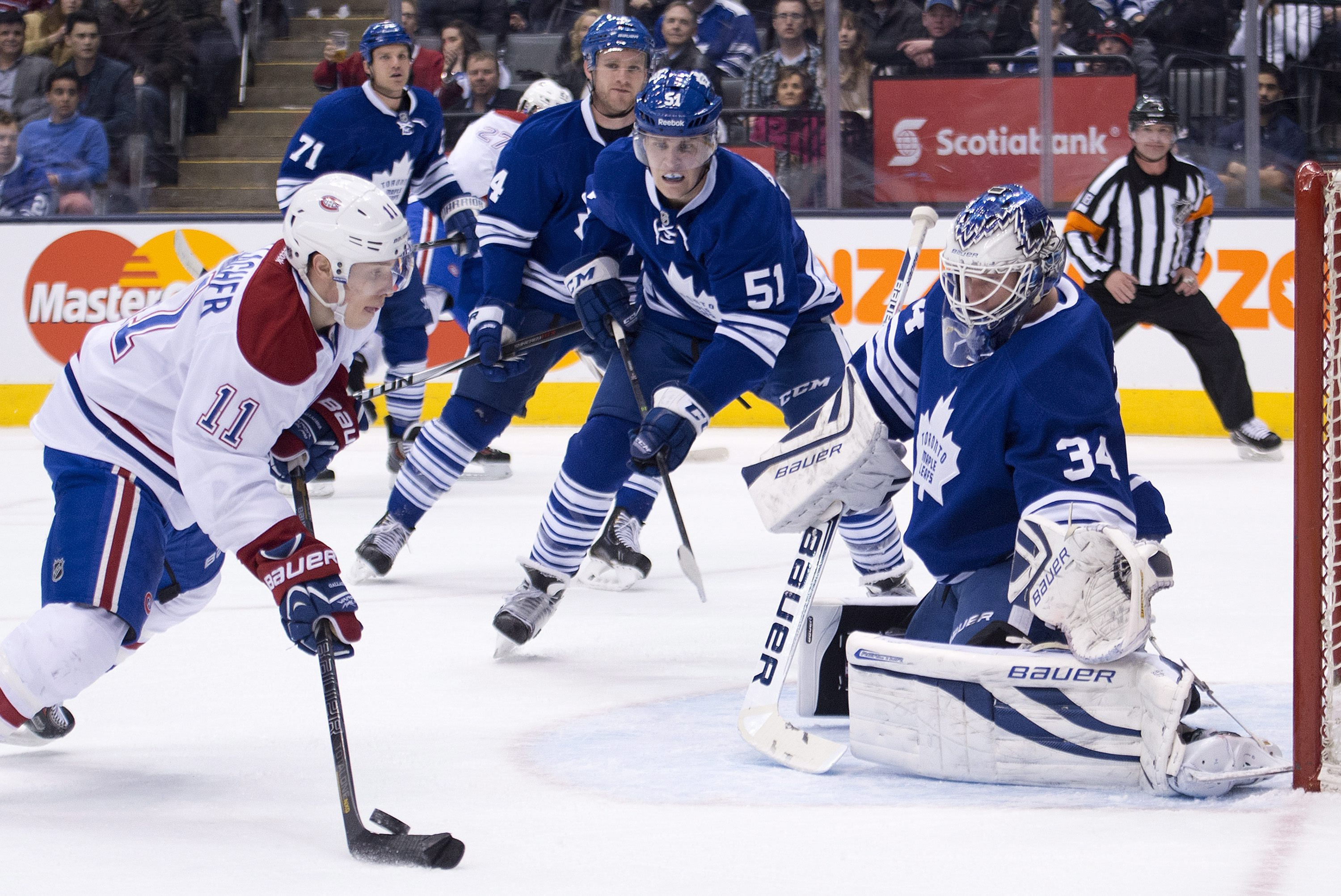 Toronto Maple goalie James Reimer, right, watches as Leafs Montreal Canadiens forward Brendan Gallagher, left, miss plays the puck during the first period NHL hockey game action in Toronto on Saturday, March 22, 2014
