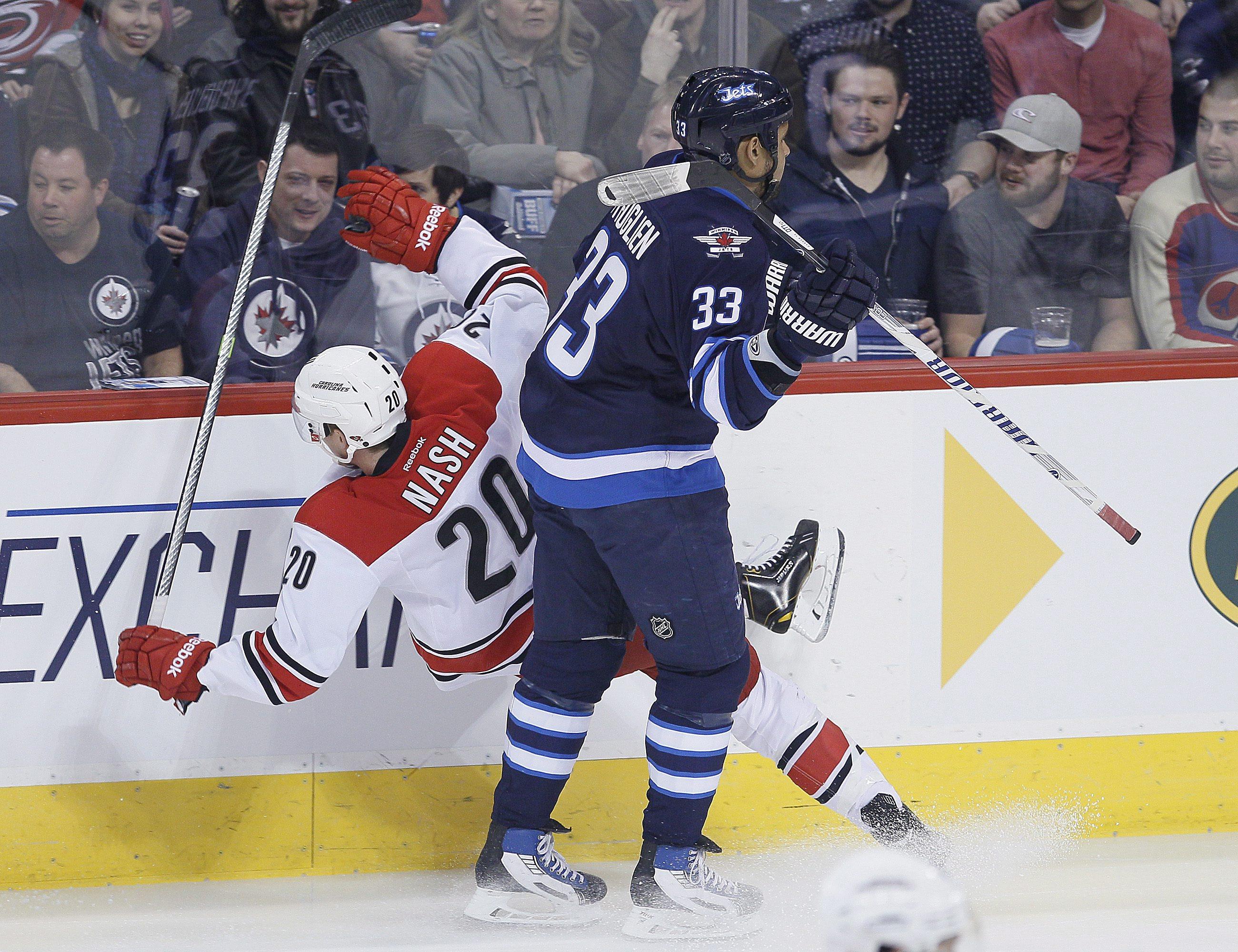 Winnipeg Jets' Dustin Byfuglien (33) dumps Carolina Hurricanes' Riley Nash (20) during the first period of an NHL hockey game, Saturday, March 22, 2014, in Winnipeg, Manitoba