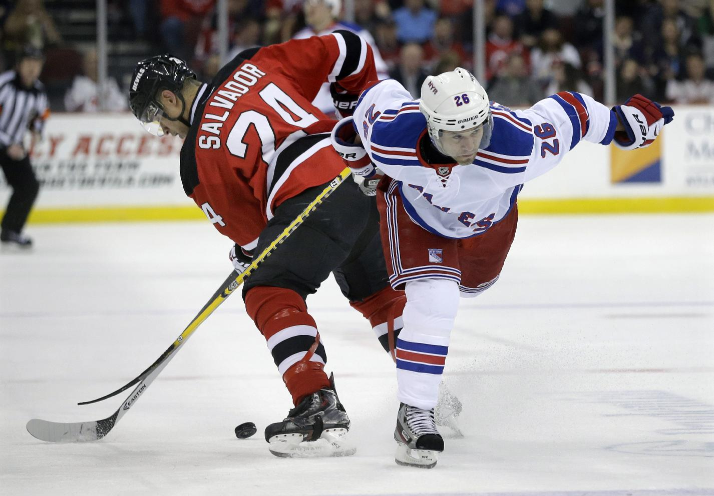 New Jersey Devils' Bryce Salvador (24) gets tied up with New York Rangers' Martin St. Louis (26) during the first period of an NHL hockey game game Saturday, March 22, 2014, in Newark, N.J