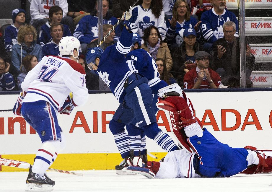 Toronto Maple Leafs forward James van Riemsdyk, center, gets called for an interference penalty after taking out Montreal Canadiens goalie Carey Price, right, during the third period of an NHL hockey game in Toronto on Saturday, March 22, 2014