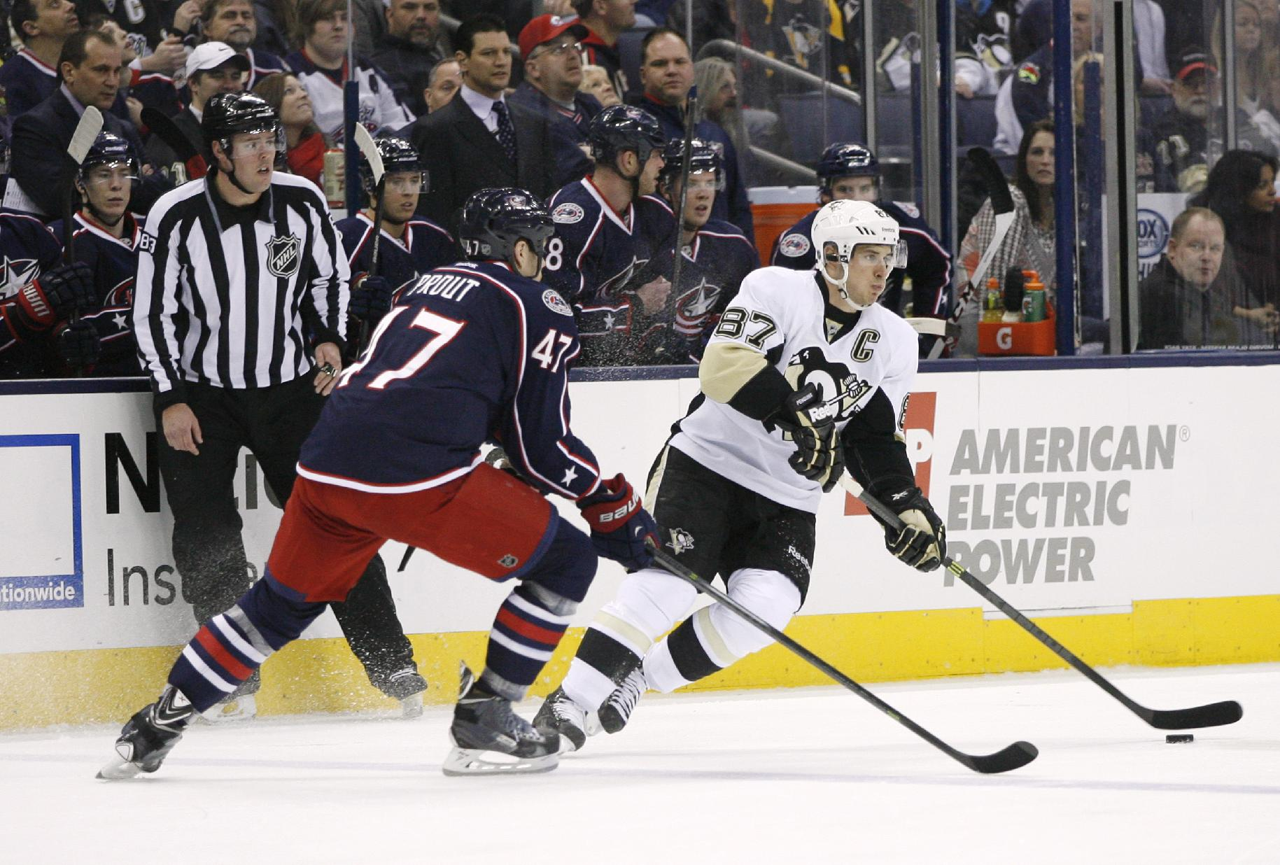 Pittsburgh Penguins' Sidney Crosby (87) keeps the puck away from Columbus Blue Jackets' Dalton Prout (47) during the first period of an NHL hockey game, Friday, March 28, 2014, in Columbus, Ohio