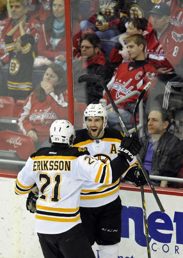 Boston Bruins center Patrice Bergeron, right, celebrates his goal with Loui Eriksson (21), of Sweden, during the third period of an NHL hockey game against the Washington Capitals, Saturday, March 29, 2014, in Washington. The Bruins won 4-2