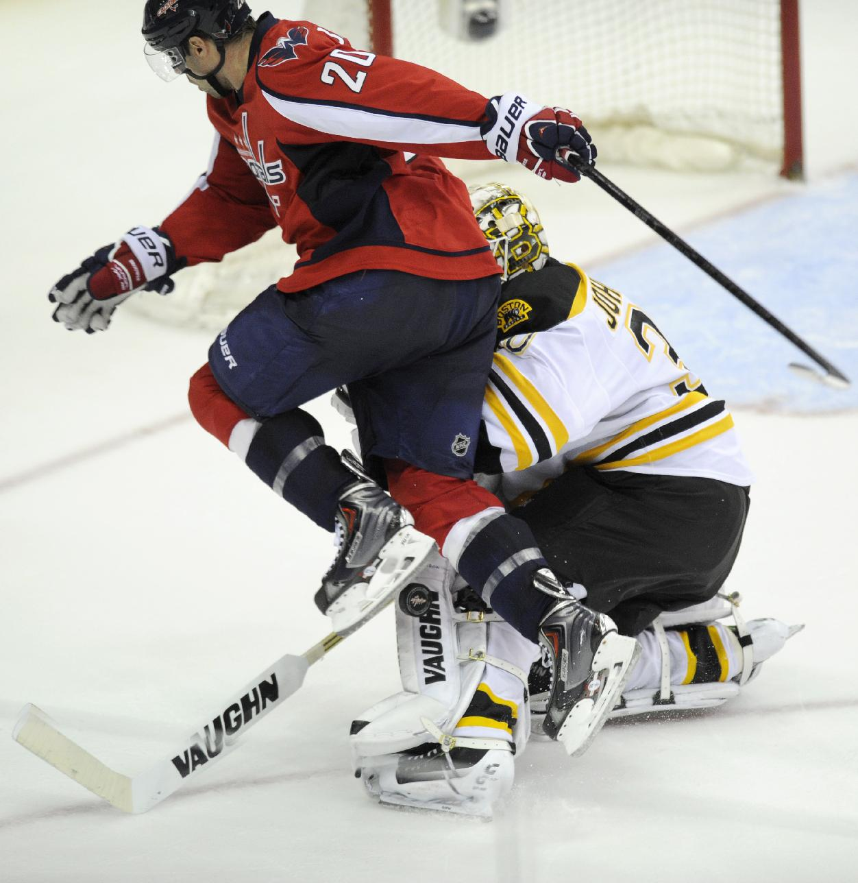 Washington Capitals right wing Troy Brouwer (20) saktes into Boston Bruins goalie Chad Johnson (30) as he went for the puck during the third period of an NHL hockey game, Saturday, March 29, 2014, in Washington. The Bruins won 4-2