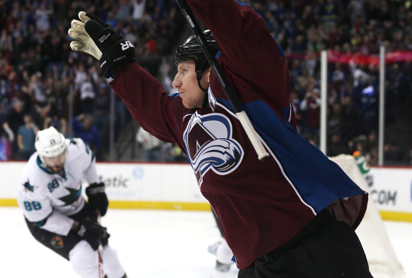 Colorado Avalanche left wing Cody McLeod, front, celebrates his short-handed goal as San Jose Sharks right wing Brent Burns reacts in the background in the first period of an NHL hockey game on Saturday, March 29, 2014, in Denver