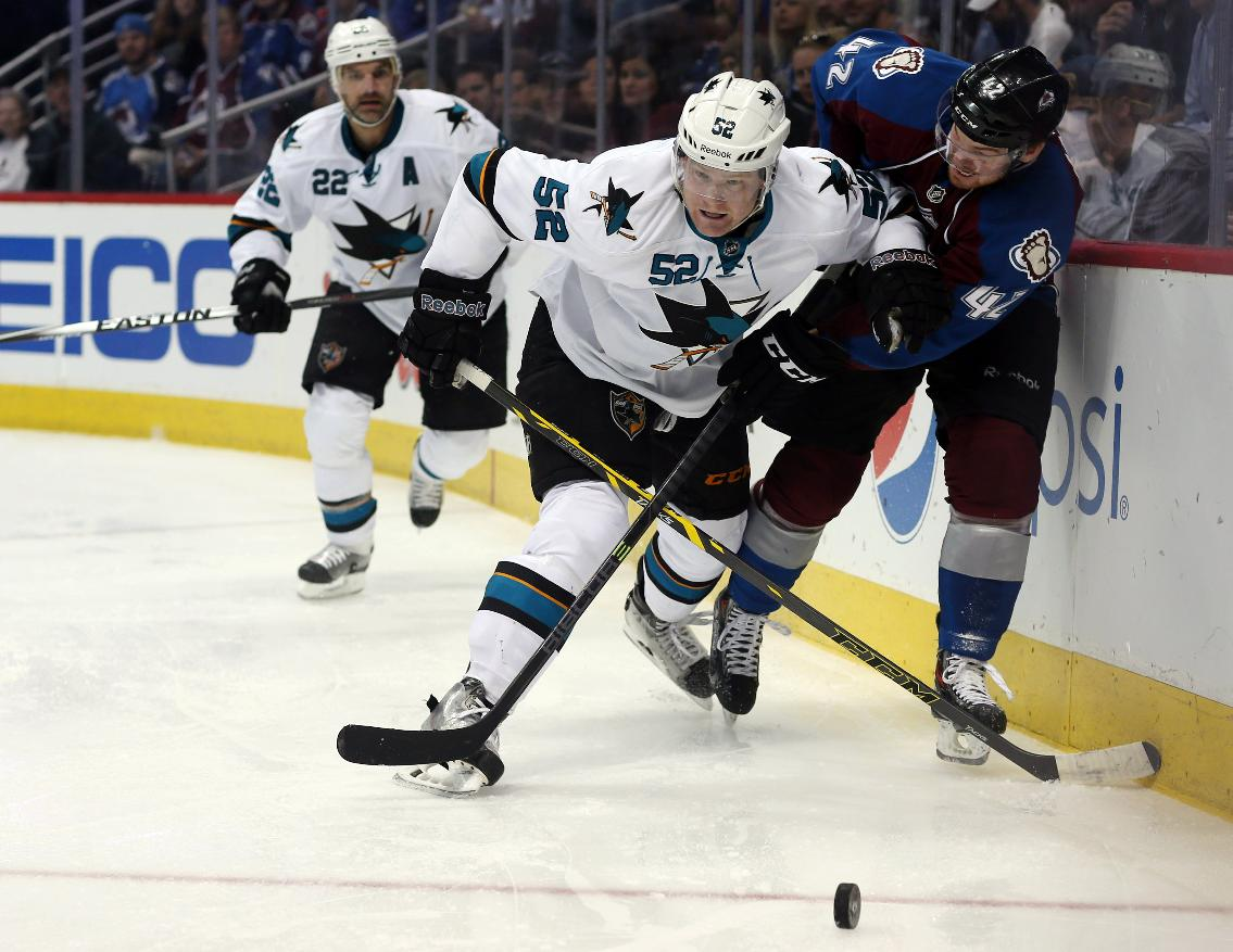 San Jose Sharks defenseman Matt Irwin, front left, battles for control of the puck with Colorado Avalanche center Brad Malone, front right, as Sharks defenseman Dan Boyle trails the play in the second period of an NHL hockey game in Denver on Saturday, March 29, 2014