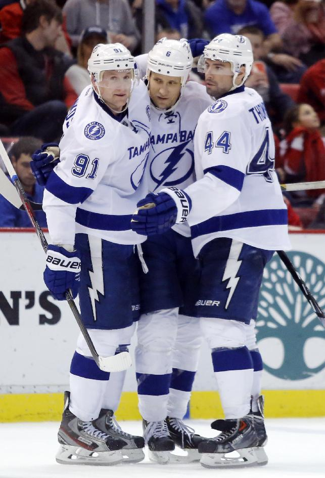 Tampa Bay Lightning's Sami Salo, center, of Finland, celebrates his third-period goal against the Detroit Red Wings with teammates Steven Stamkos (91) and Nate Thompson (44) during an NHL hockey game  onSunday, March 30, 2014, in Detroit