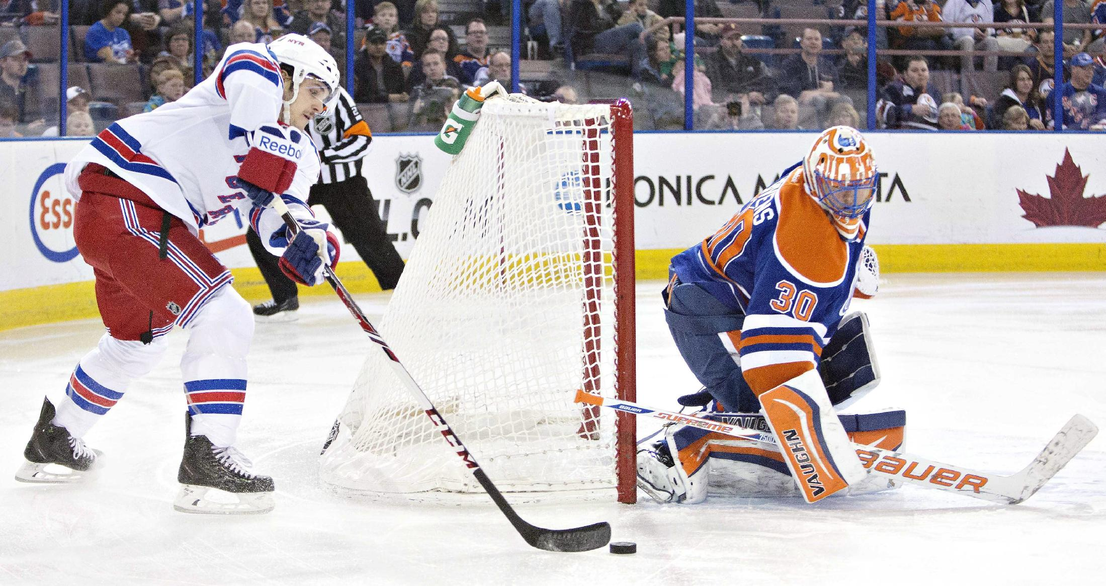 New York Rangers Daniel Carcillo (13) is stopped by Edmonton Oilers Ben Scrivens (30) during first period NHL hockey action in Edmonton, Alberta., on Sunday March 30, 2014