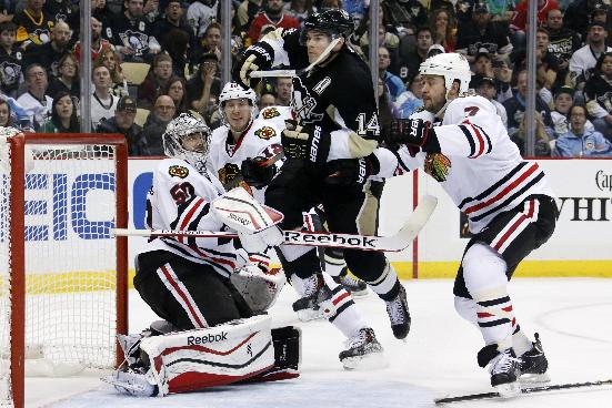 Pittsburgh Penguins' Chris Kunitz (14) leaps across the goal crease between Chicago Blackhawks goalie Corey Crawford (50) and Brent Seabrook (7) in the second period of an NHL hockey game in Pittsburgh, Sunday, March 30, 2014