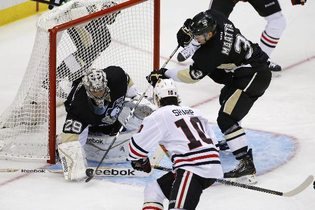 Pittsburgh Penguins' Olli Maatta (3) clears a loose puck from in front of goalie Marc-Andre Fleury (29) before Chicago Blackhawks' Patrick Sharp (10) can get his stick on it in the third period of an NHL hockey game in Pittsburgh, Sunday, March 30, 2014. The Penguins won 4-1