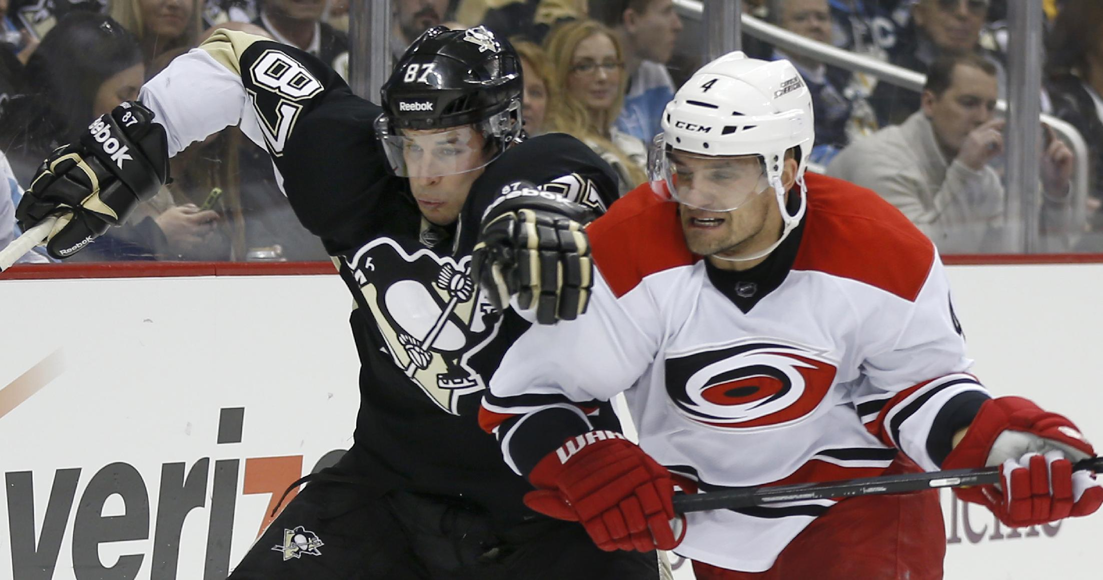 Pittsburgh Penguins' Sidney Crosby (87) and Carolina Hurricanes' Andrej Sekera, of Slovakia, chase after a puck along the bords  during the second period of an NHL hockey game onTuesday, April 1, 2014, in Pittsburgh