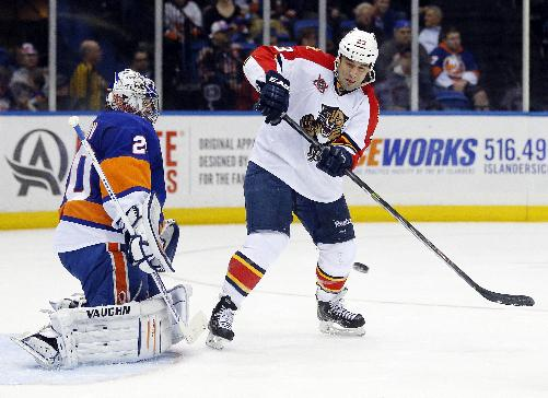 New York Islanders goalie Evgeni Nabokov (20) makes a save on a tip-in attempt by Florida Panthers center Scott Gomez (23) during the third period of an NHL hockey game at Nassau Coliseum in Uniondale, N.Y., Tuesday, April 1, 2014. The Islanders won 4-2