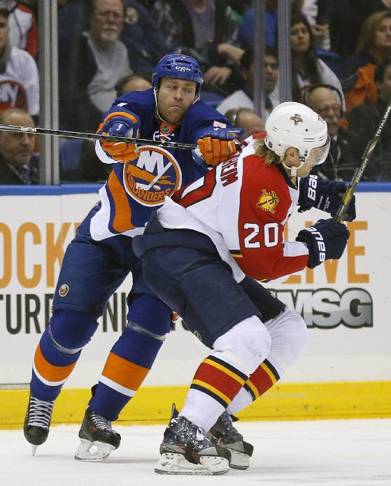 New York Islanders defenseman Matt Carkner (7) checks Florida Panthers left wing Sean Bergenheim (20) during the second period of an NHL hockey game at Nassau Coliseum in Uniondale, N.Y., Tuesday, April 1, 2014. The Islanders won 4-2