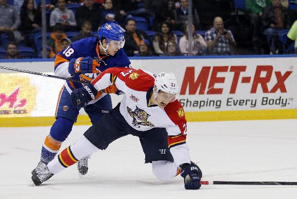 New York Islanders center Ryan Strome (18) knocks Florida Panthers center Nick Bjugstad (27) to the ice in the first period of an NHL hockey game at Nassau Coliseum in Uniondale, N.Y., Tuesday, April 1, 2014.  The Islanders won 4-2