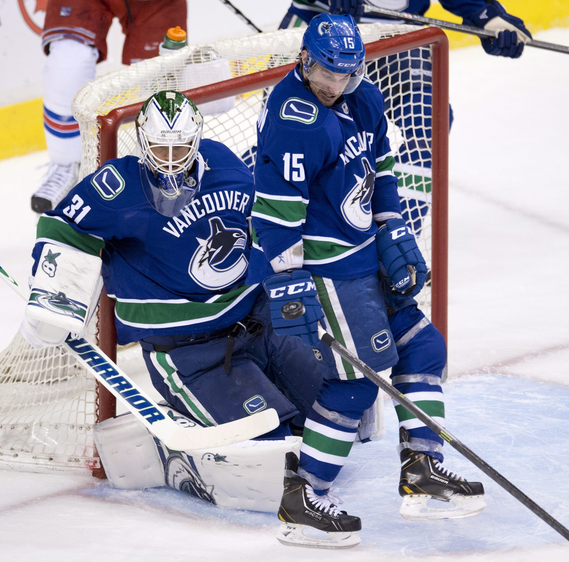 Vancouver Canucks goalie Eddie Lack (31) and Brad Richardson (15) stop a shot from the New York Rangers during the second period of NHL action in Vancouver, British Columbia, Tuesday, April 1, 2014