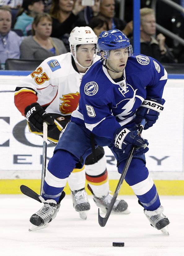 Tampa Bay Lightning center Tyler Johnson (9) looks to pass after stealing the puck from Calgary Flames center Sean Monahan (23) during the first period of an NHL hockey game on Thursday, April 3, 2014, in Tampa, Fla
