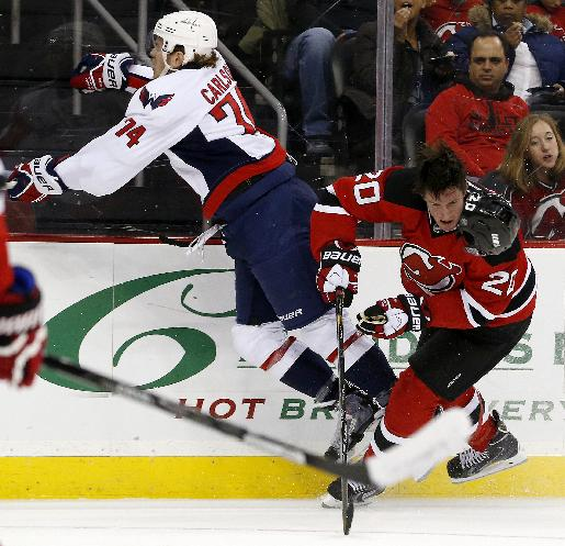 New Jersey Devils center Ryan Carter (20) loses his helmet after colliding with Washington Capitals defenseman John Carlson (74) during the first period of an NHL hockey game, Friday, April 4, 2014, in Newark, N.J