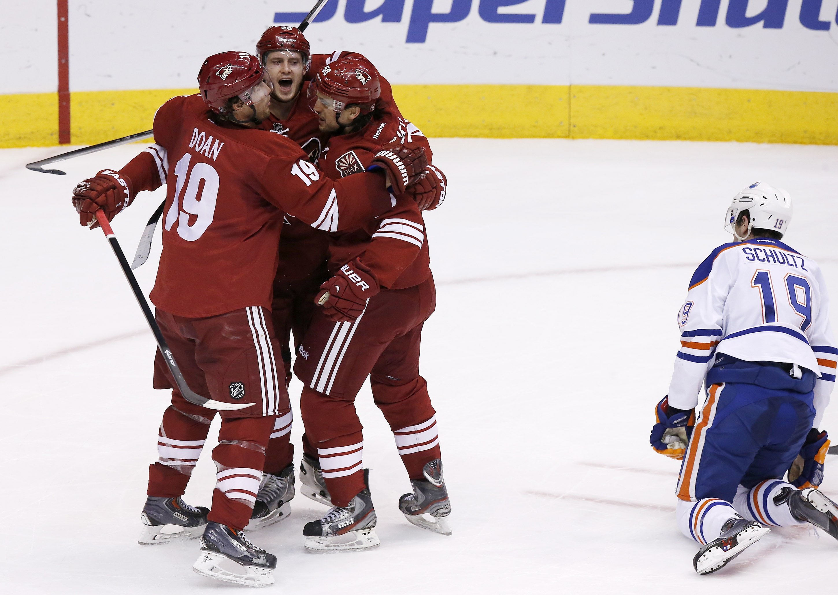 Phoenix Coyotes' Oliver Ekman-Larsson, second from left, of Sweden, celebrates his goal with teammates Shane Doan, left, and Antoine Vermette as Edmonton Oilers' Justin Schultz (19) kneels on the ice during the second period of an NHL hockey game, Friday, April 4, 2014, in Glendale, Ariz