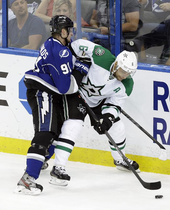 Tampa Bay Lightning center Steven Stamkos (91) pushes Dallas Stars defenseman Trevor Daley (6) into the boards during the first period of an NHL hockey game on Saturday, April 5, 2014, in Tampa, Fla