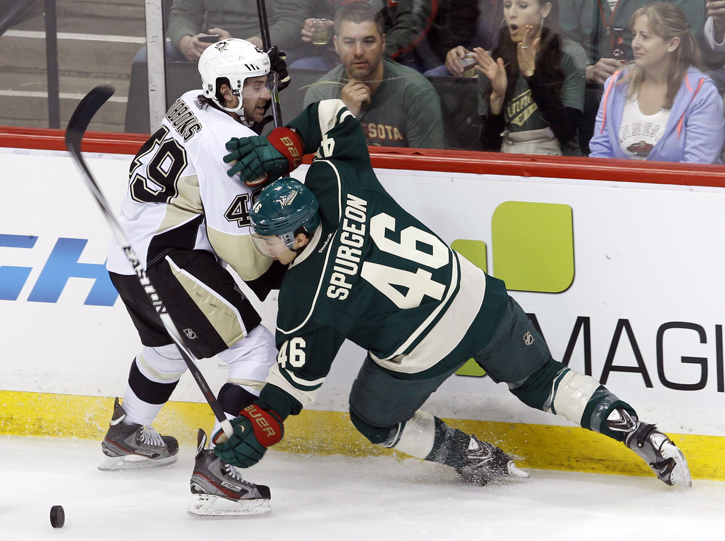 Minnesota Wild defenseman Jared Spurgeon (46) falls as he and Pittsburgh Penguins center Brian Gibbons (49) chase the puck during the first period of an NHL hockey game in St. Paul, Minn., Saturday, April 5, 2014