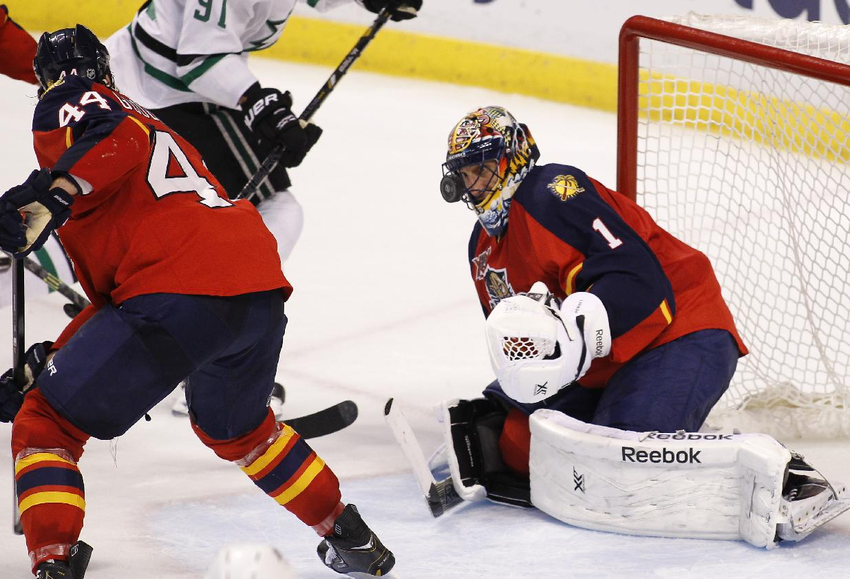 Florida Panthers goalie Roberto Luongo (1) is hit with the puck as teammate Erik Gudbranson (44) helps defend during the third period of an NHL hockey game against the Dallas Stars in Sunrise, Fla., Sunday, April 6, 2014. Florida won 3-2