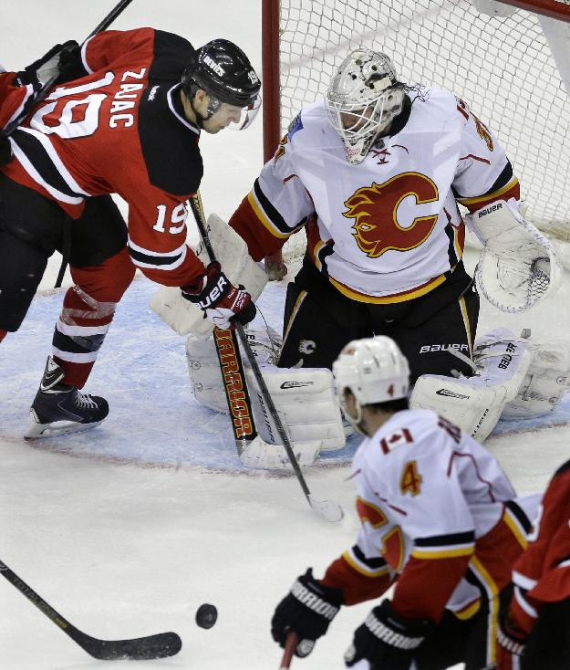 Calgary Flames goalie Karri Ramo, top right, of Finland, blocks a shot by New Jersey Devils' Travis Zajac (19)during the third period of an NHL hockey game in Newark, N.J., Monday, April 7, 2014. The Flames won 1-0