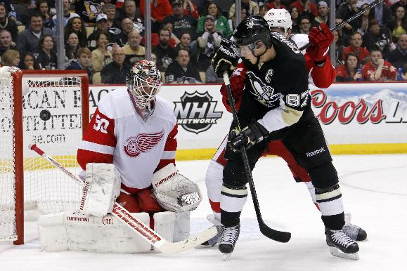 Pittsburgh Penguins' Sidney Crosby (87) can't get a shot past Detroit Red Wings goalie Jonas Gustavsson (50) and Red Wings' Danny DeKeyser, rear, during the second period of an NHL hockey game in Pittsburgh, Wednesday, April 9, 2014