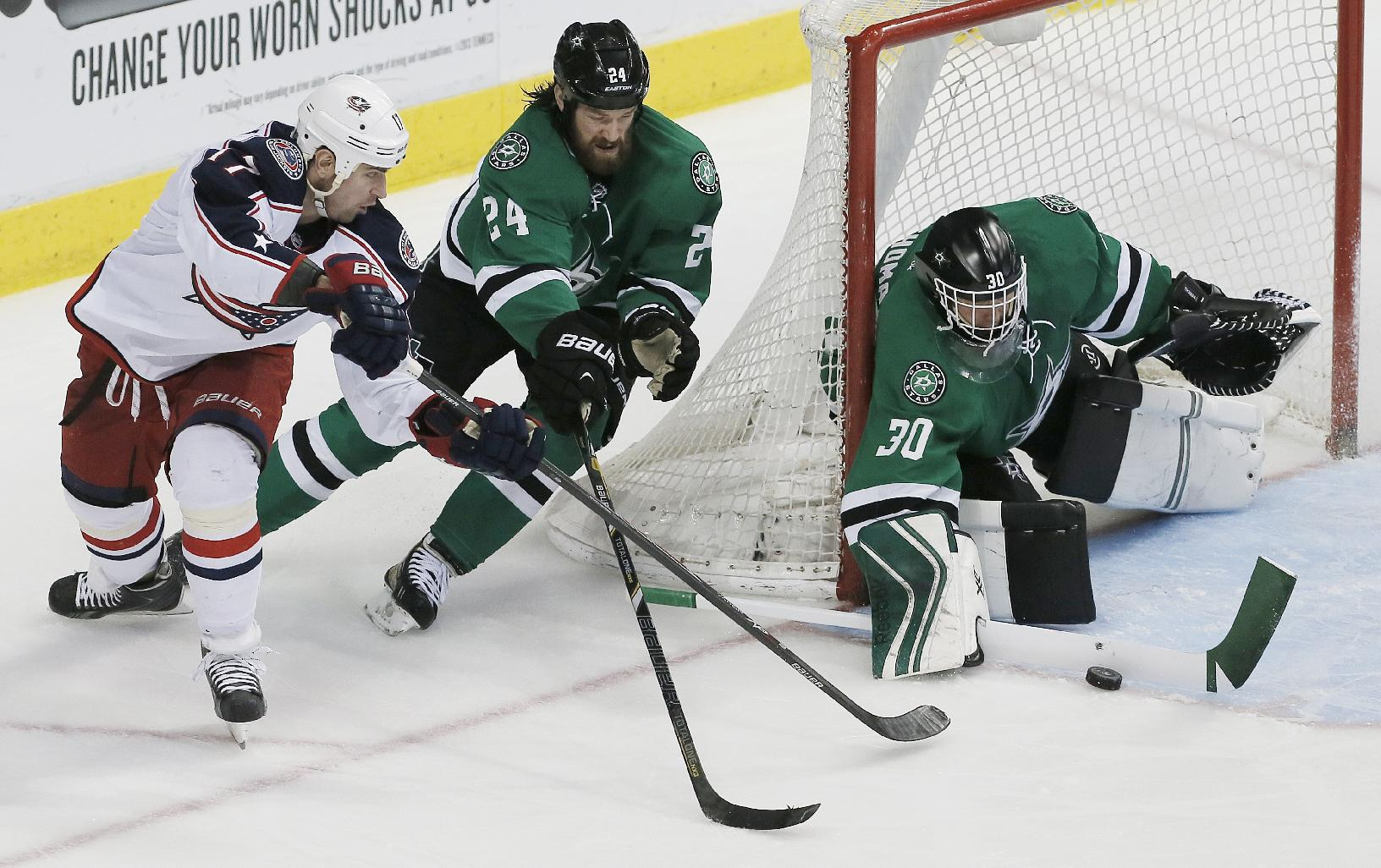 Columbus Blue Jackets center Brandon Dubinsky (17) attempts a backhanded shot as Dallas Stars defenseman Jordie Benn (24) and goalie Tim Thomas (30) defend during the second period of an NHL hockey game on Wednesday, April 9, 2014, in Dallas