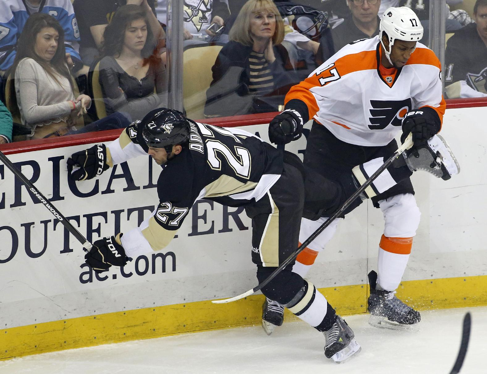 Philadelphia Flyers' Wayne Simmonds (17) collides with Pittsburgh Penguins' Craig Adams (27) during the first period of an NHL hockey game in Pittsburgh, Saturday, April 12, 2014