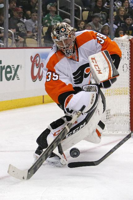 Philadelphia Flyers goalie Steve Mason (35) clears the puck during the second period of an NHL hockey game against the Pittsburgh Penguins in Pittsburgh, Saturday, April 12, 2014