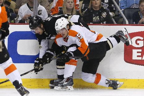 Philadelphia Flyers' Tye McGinn (15) collides with Pittsburgh Penguins' Brandon Sutter (16) in the second period of an NHL hockey game in Pittsburgh, Saturday, April 12, 2014
