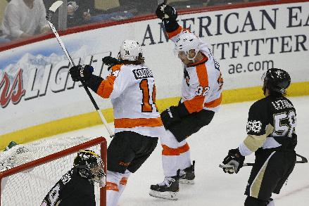 Philadelphia Flyers' Mark Streit (32) celebrates his game-winning overtime goal past Pittsburgh Penguins goalie Marc-Andre Fleury (29) with teammate Sean Couturier (14) during an NHL hockey game in Pittsburgh, Saturday, April 12, 2014. The Flyers won 4-3 in overtime