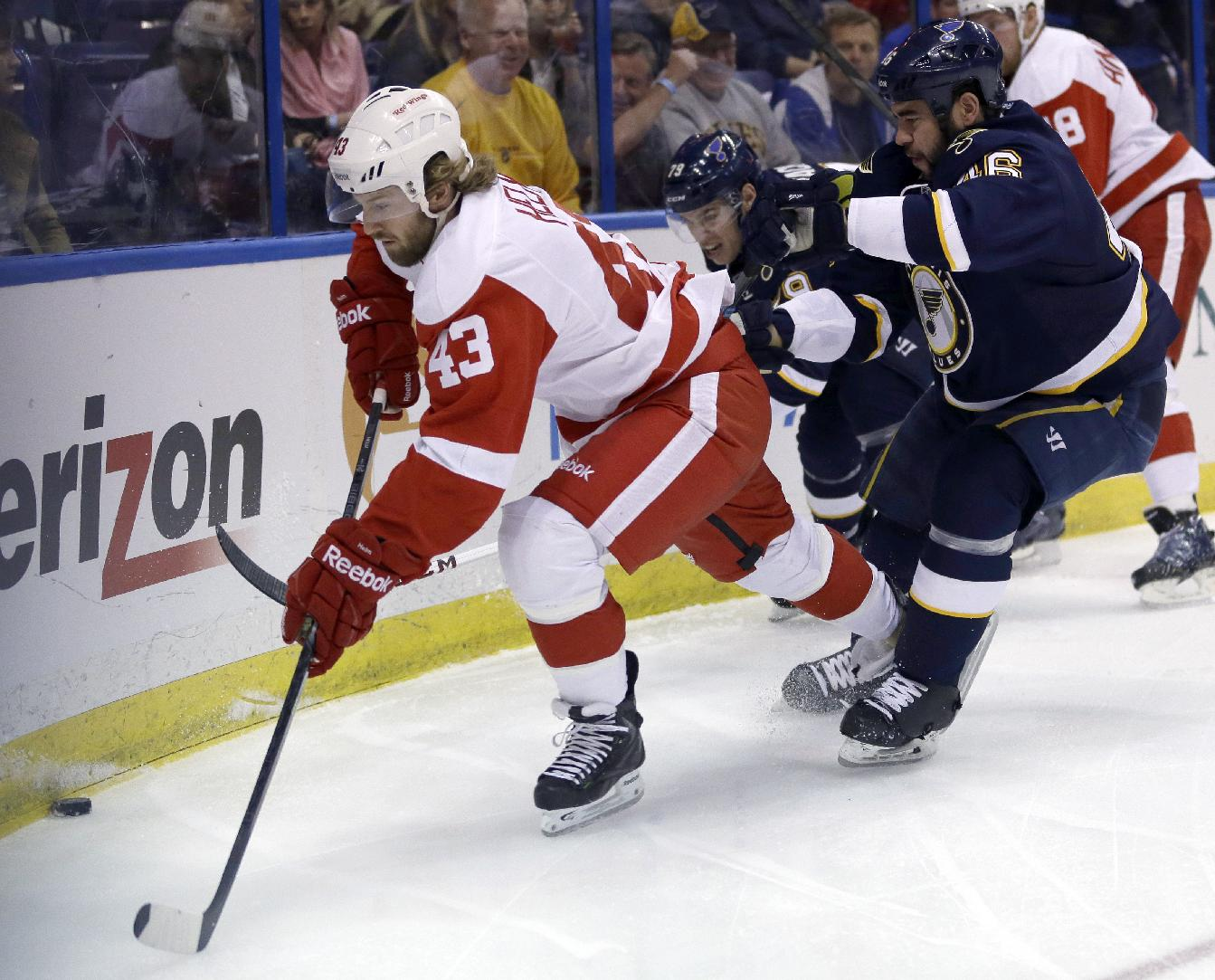 Detroit Red Wings' Darren Helm, left, reaches for a loose puck as St. Louis Blues' Adam Cracknell, center rear, and Roman Polak, of the Czech Republic, defend during the first period of an NHL hockey game Sunday, April 13, 2014, in St. Louis