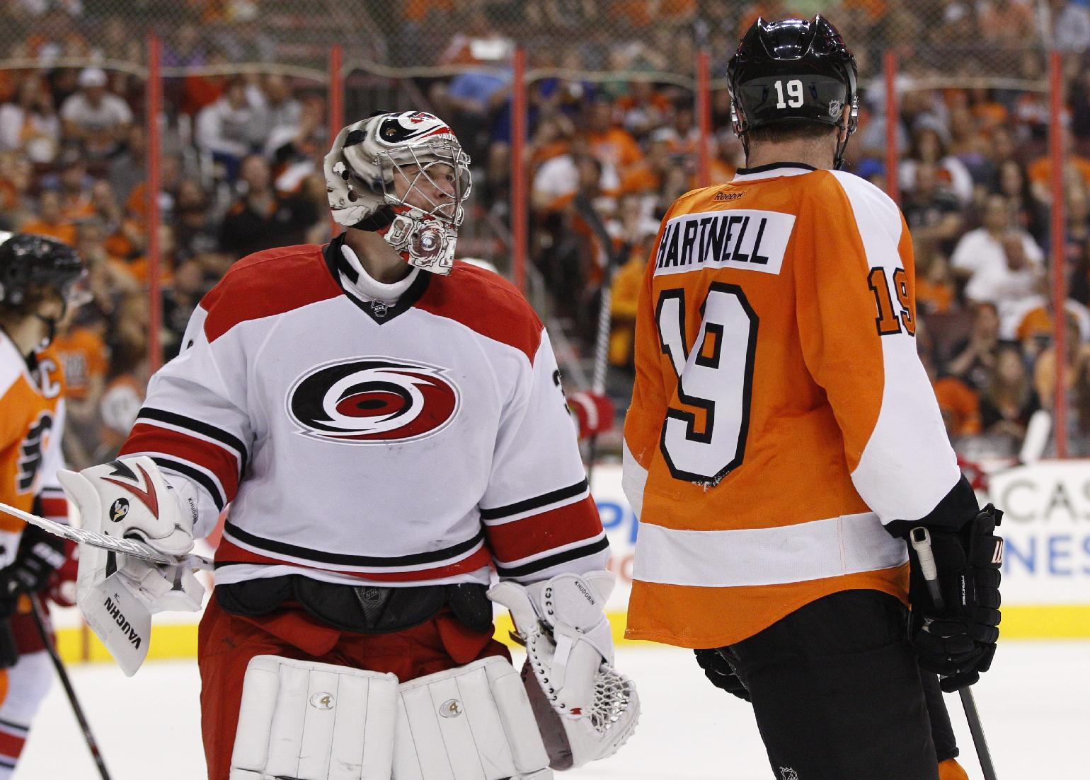 Carolina Hurricanes' Anton Khudobin, left, of Russia has some words with Philadelphia Flyers' Scott Hartnell, left, after Hartnell collided with Khudobin in the goal during the second period of an NHL hockey game, Sunday, April 13, 2014, in Philadelphia