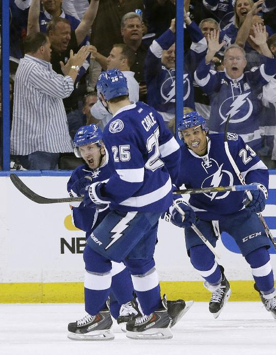 Tampa Bay Lightning right wing Nikita Kucherov (86), of Russia, celebrates with teammates Matt Carle (25) and J.T. Brown after scoring against the Montreal Canadiens during the first period of Game 1 of a first-round NHL hockey playoff series on Wednesday, April 16, 2014, in Tampa, Fla